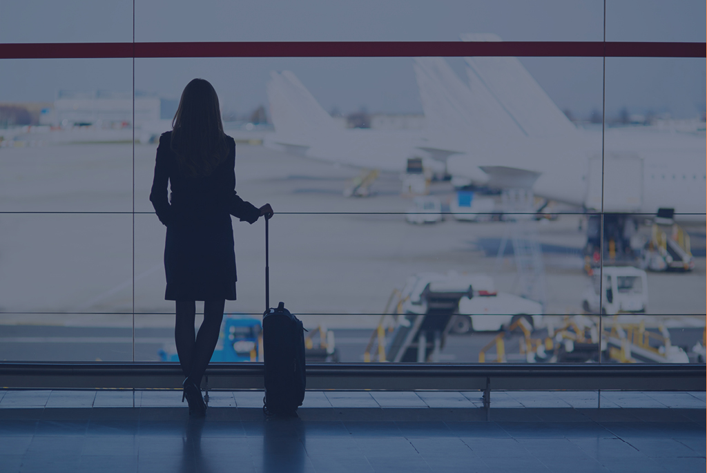 back of female with suitcase at airport viewing planes
